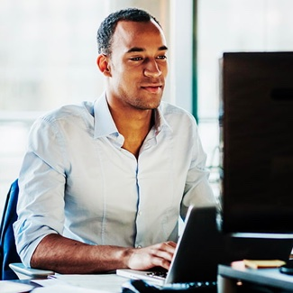 Man smiling sitting at a desk typing on a laptop