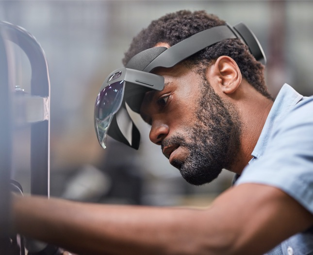 Man wearing an AR headset working on a machine