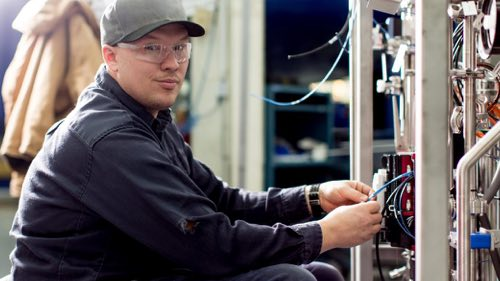 Person wearing safety glasses working on a machine