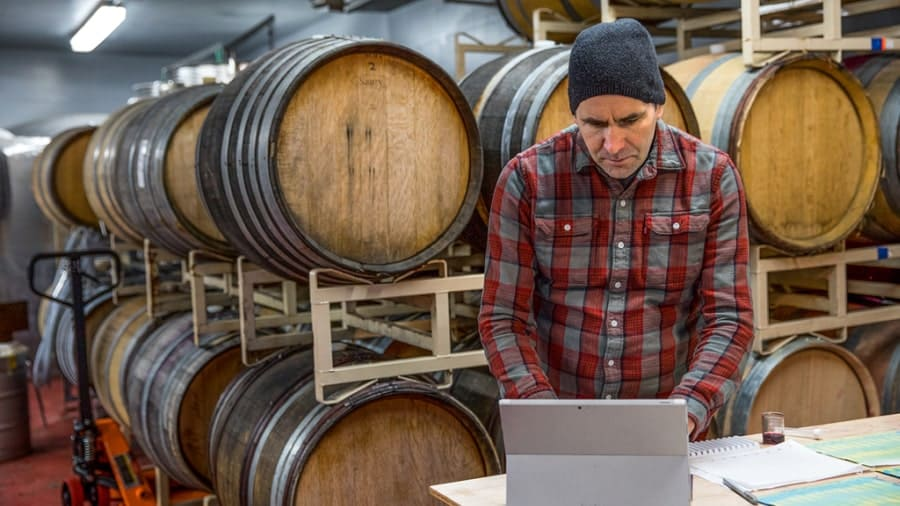 Man working on device in front of wooden barrels