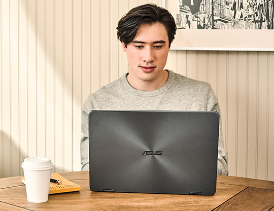 Person sitting at a table using a laptop