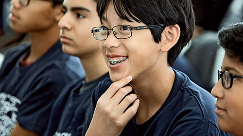 Young boy wearing glasses, smiling amongst other students
