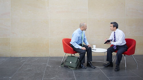 Two businessmen having a meeting in waiting area of office