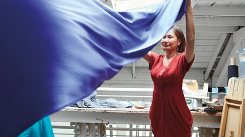 Woman shaking out long piece of blue fabric