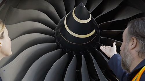 Two colleagues inspecting an airplane engine