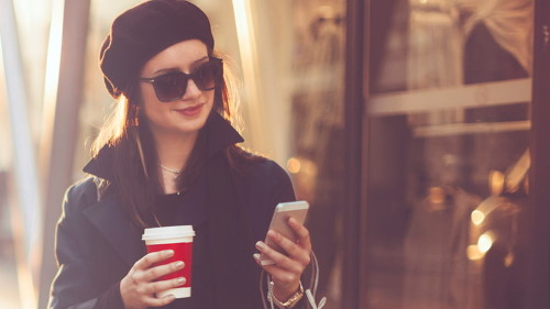 Person in black coat holding a phone and coffee cup