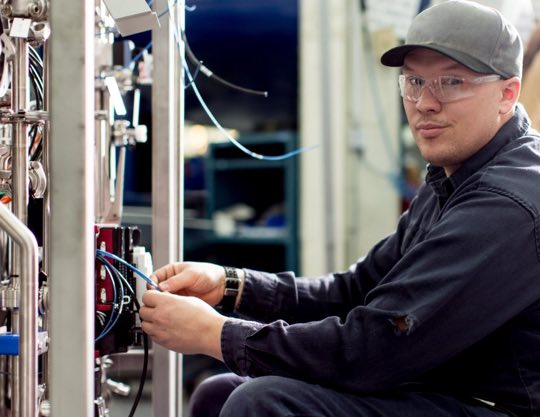 Technician wearing safety glasses working on a machine