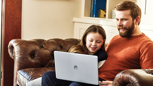 Father and daughter sitting on couch using a laptop