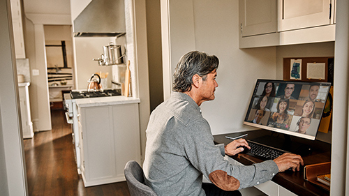 Person sitting in kitchen working on a computer