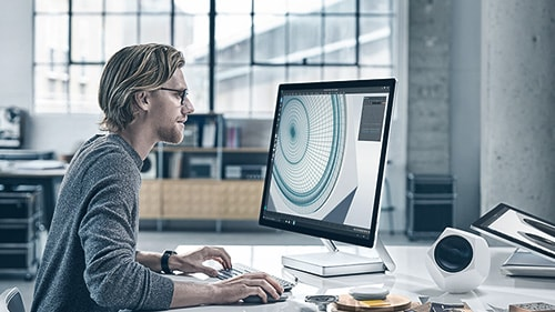 Image of a man working at a Surface Studio