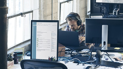 Image of a man working at desk with headphones on