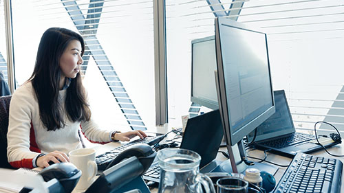 Image of woman working at desk with coffee mug