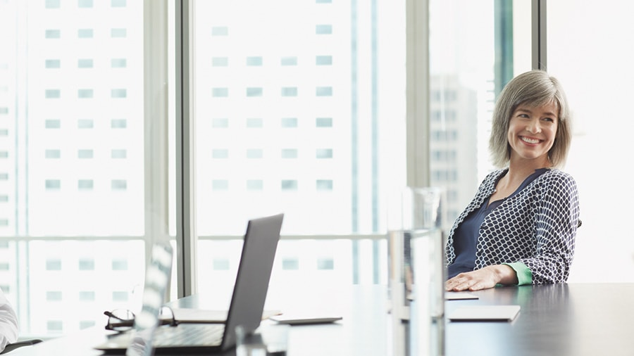 Image of a woman sitting and smiling at conference table