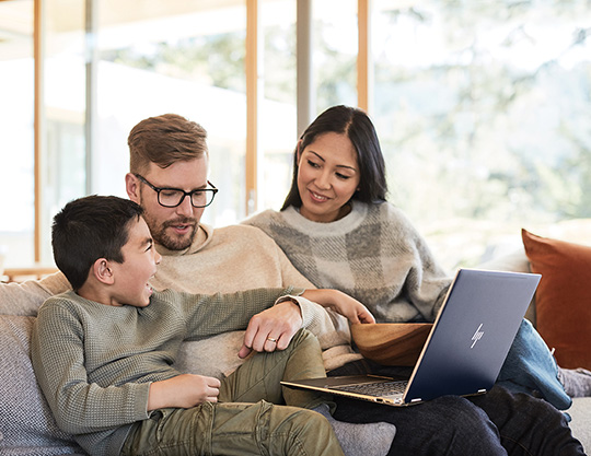 Family sitting on couch together using a laptop