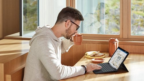 Person in kitchen working on a laptop at a table