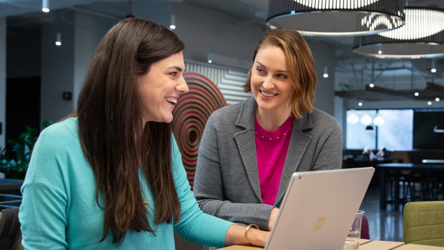 Two people smile as they work together in front of a laptop