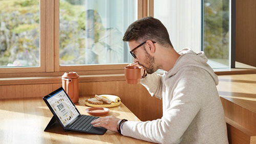 Person working on laptop over breakfast