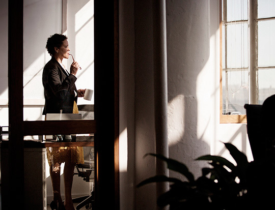 Business woman drinking coffee and looking out window