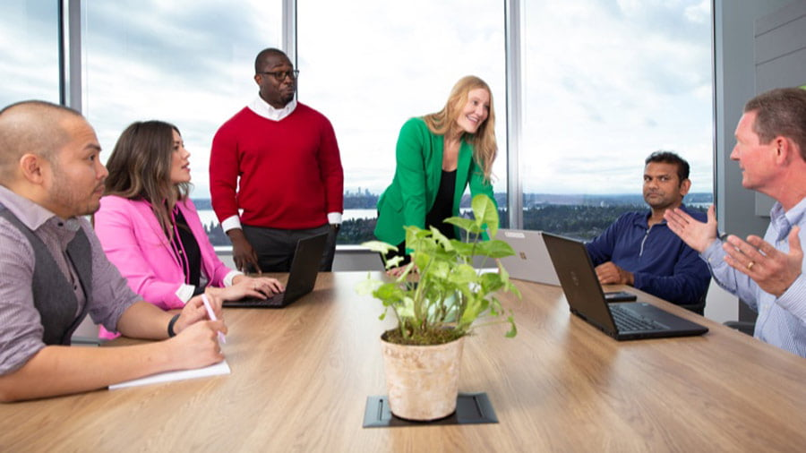 A team of people work together around a conference table