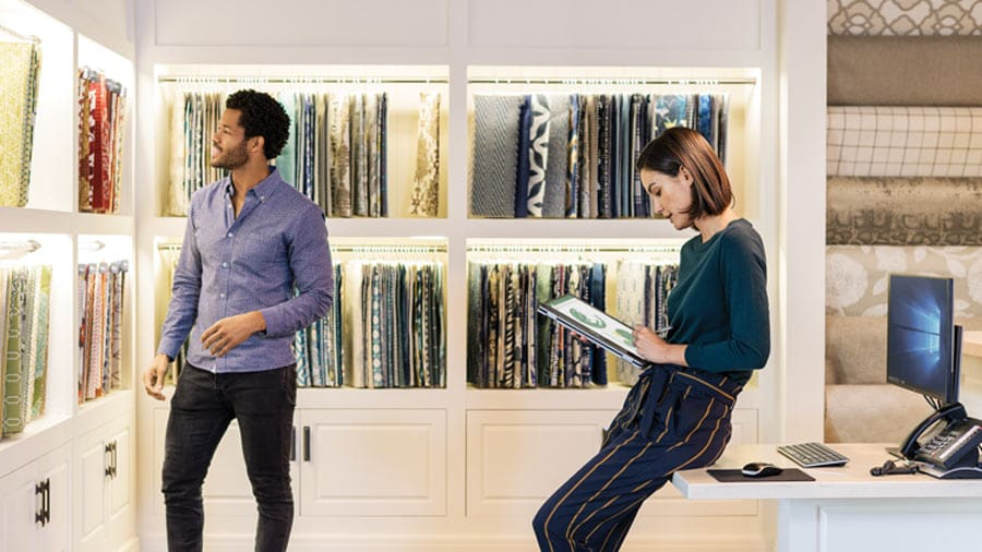 In a showroom, one person looks at fabric samples while the other consults a tablet