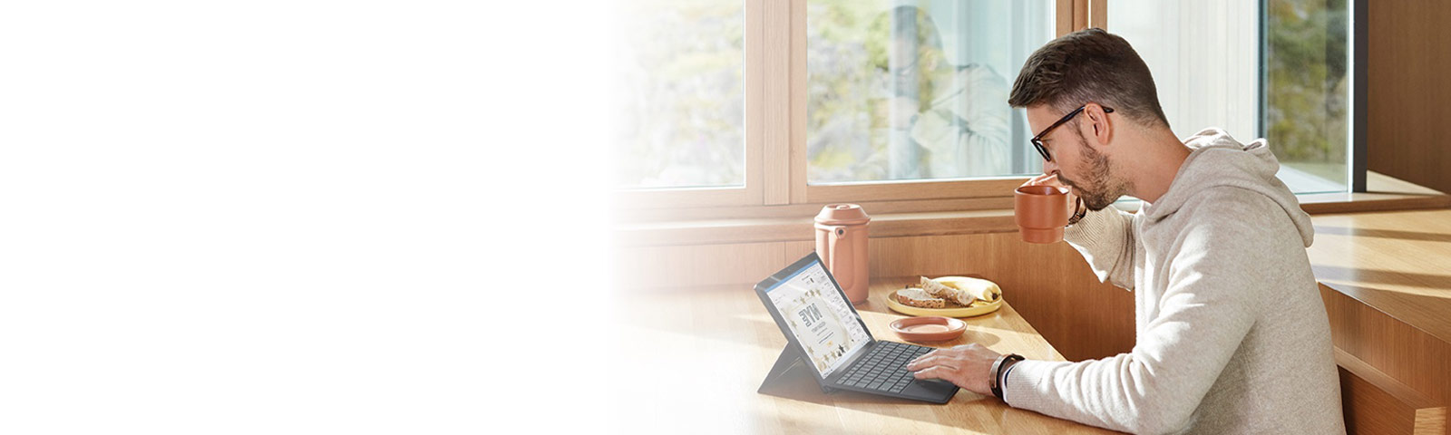 Person works on computer over breakfast in a sunny room