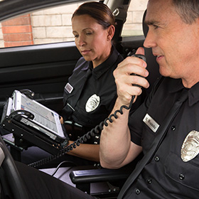 Two police officers use Microsoft at work