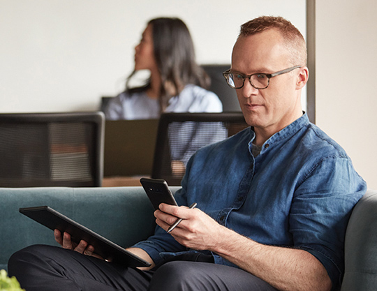 Person looking at phone and tablet in open office setting