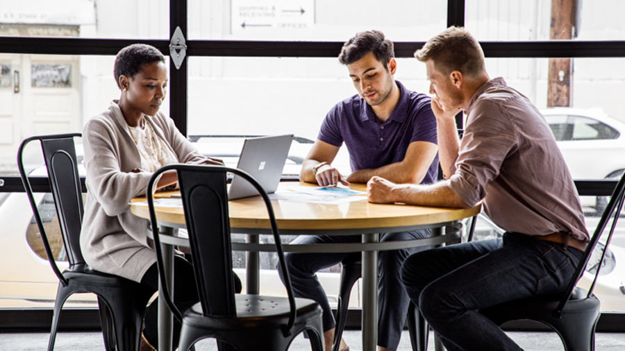 Three people work at a table