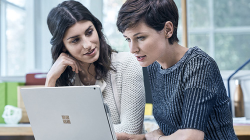 Two women looking at a Microsoft Surface
