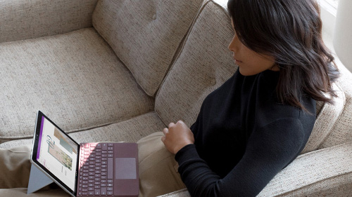 Woman using Microsoft Surface Pro on the couch