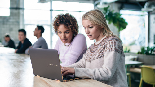 Two women looking at one laptop