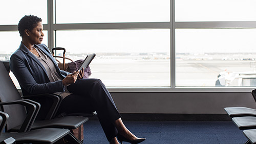 Woman sitting in airport working on tablet
