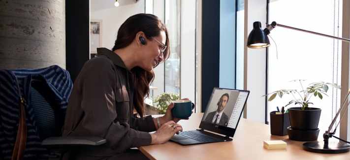 Woman drinking from a mug talking on a video call