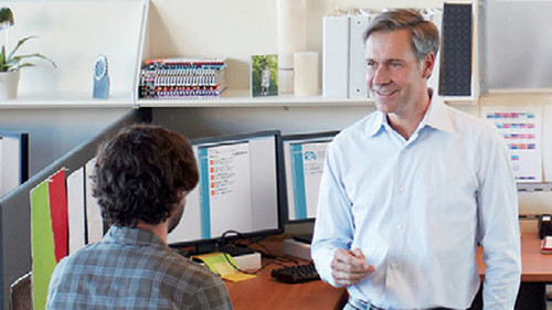 Man addressing coworker in cubicle
