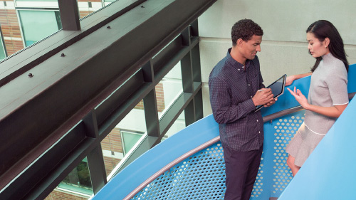 Man working on tablet while talking to coworker on stairs