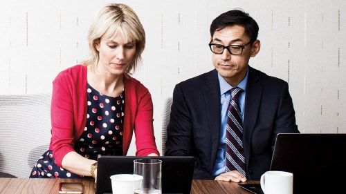 Man watching woman working on laptop