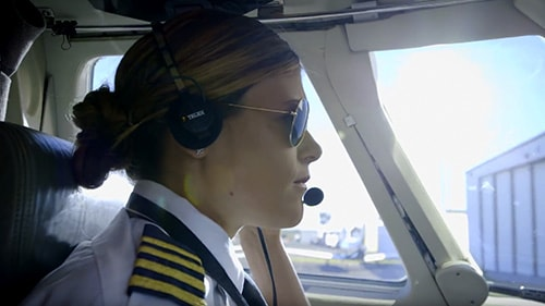 Woman pilot with sunglasses and headset