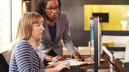 Woman training coworker at computer