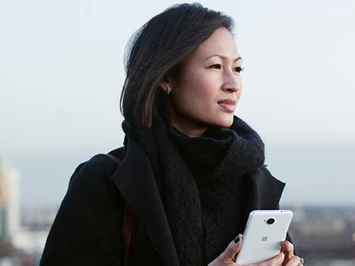 Woman standing outside looking at view and holding cellphone