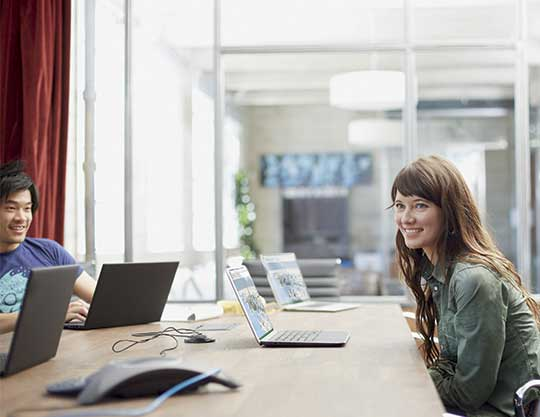 Woman smiling sitting in front of computer during meeting