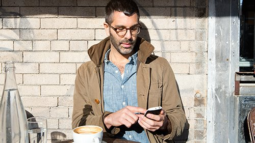 Man working on smartphone outside