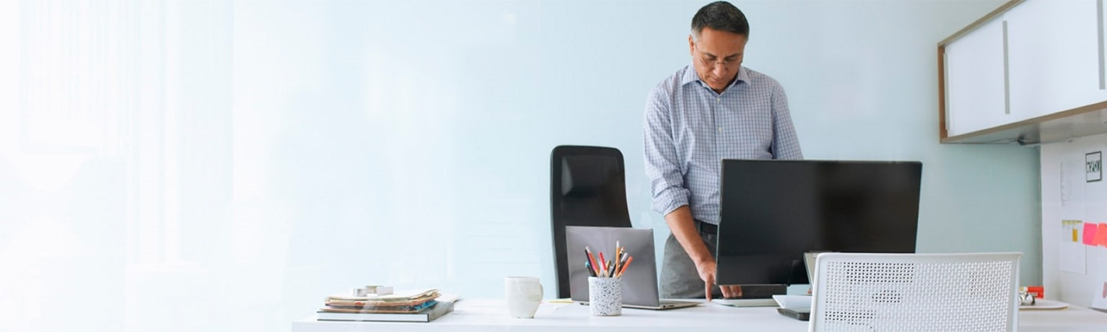 Man standing while working on computer at desk