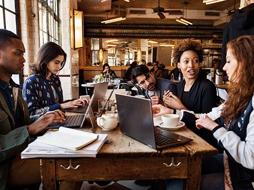 Students meeting and working in a cafe