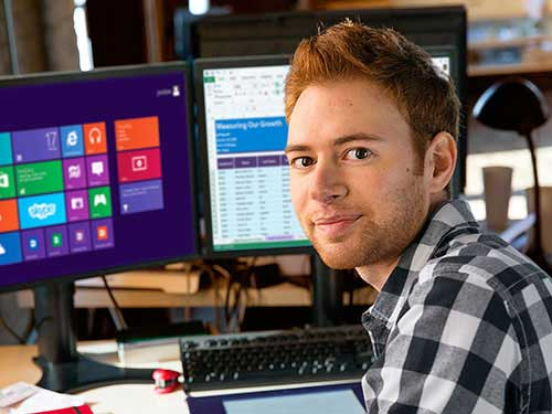 Image of man posing for photo in front of desktop computers