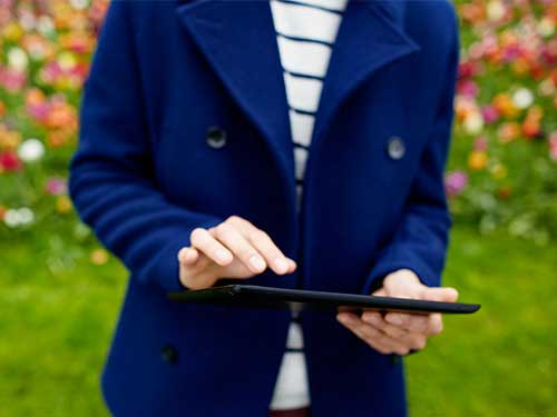 Image of man working on tablet standing outside