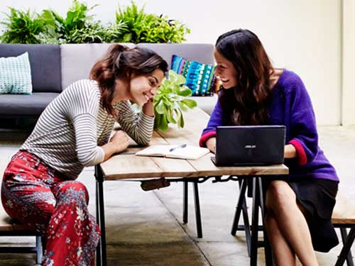 Image of two females working outside on laptop computer