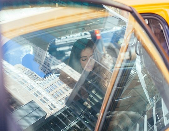 Reflection of woman sitting in car