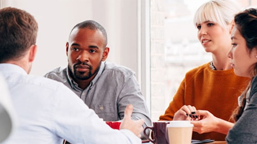 Coworkers crowded around table, talking and drinking coffee