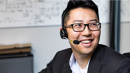 Man smiling wearing glasses and headset