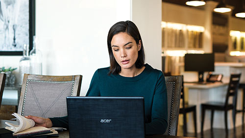 Woman working on laptop in library